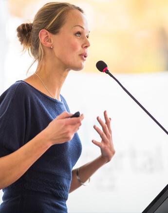 Eine blonde Frau spricht vor einem Stabmikrofon und gestikuliert.